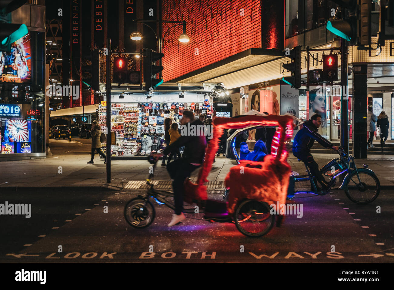 London, UK - March 9, 2019: Colourful rickshaws riding on Oxford Street, London, at night. Oxford Street if one of the most famous streets in London,  - Stock Image