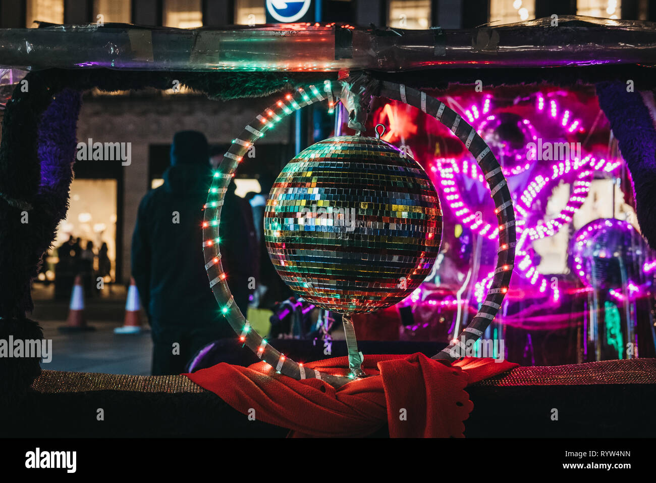 London, UK - March 9, 2019: Colourful disco ball on a rickshaw on Oxford Street, London, at night. Oxford Street if one of the most famous streets in  - Stock Image