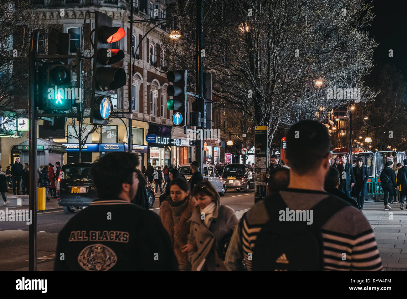 London, UK - March 9, 2019: People walking on Oxford Street, London, in the evening. Oxford street is one of the most famous shopping streets in Londo - Stock Image