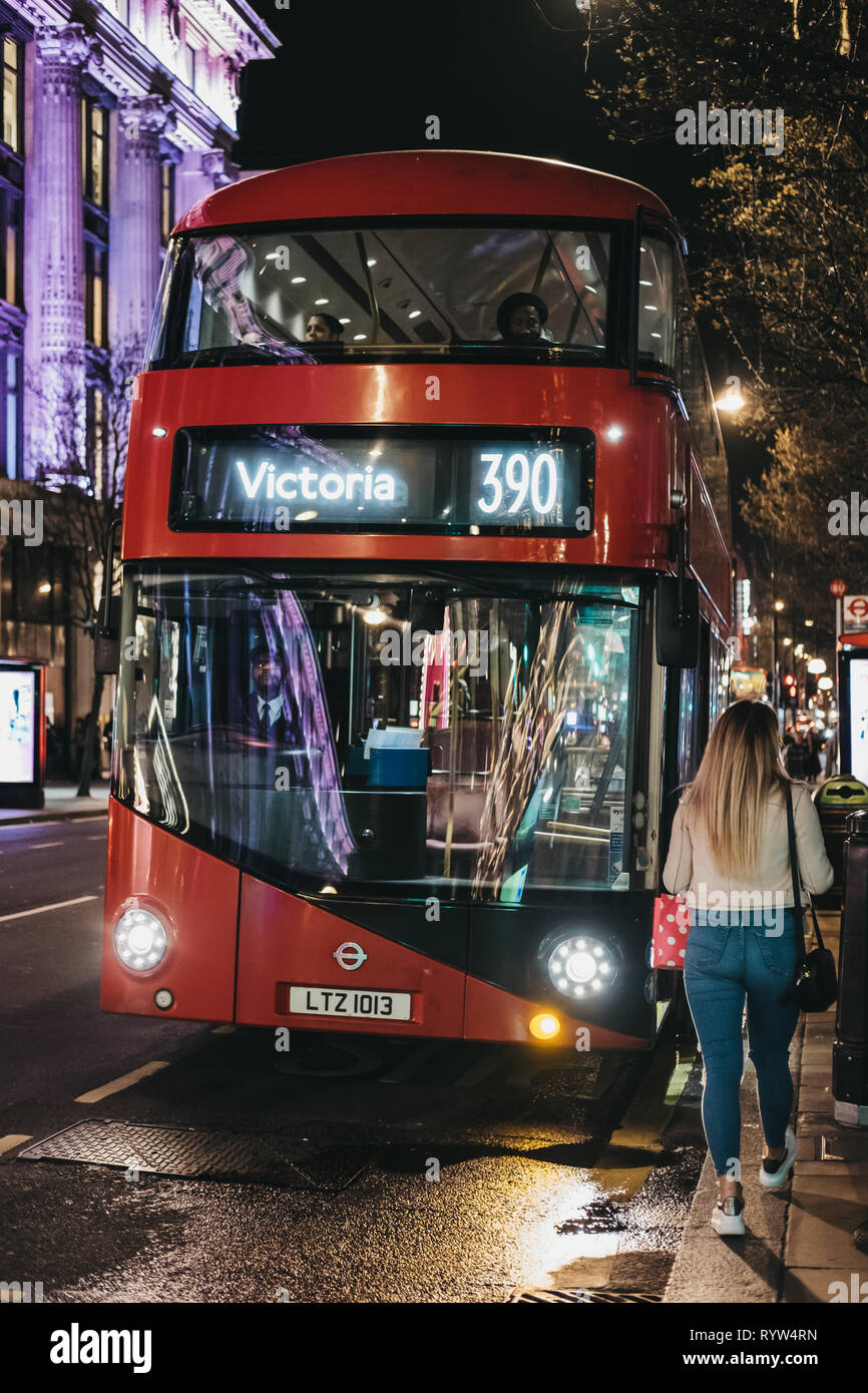London, UK - March 9, 2019: People boarding 390 bus to Victoria on Oxford Street, London, UK. Oxford Street if one of the most famous streets in Londo - Stock Image