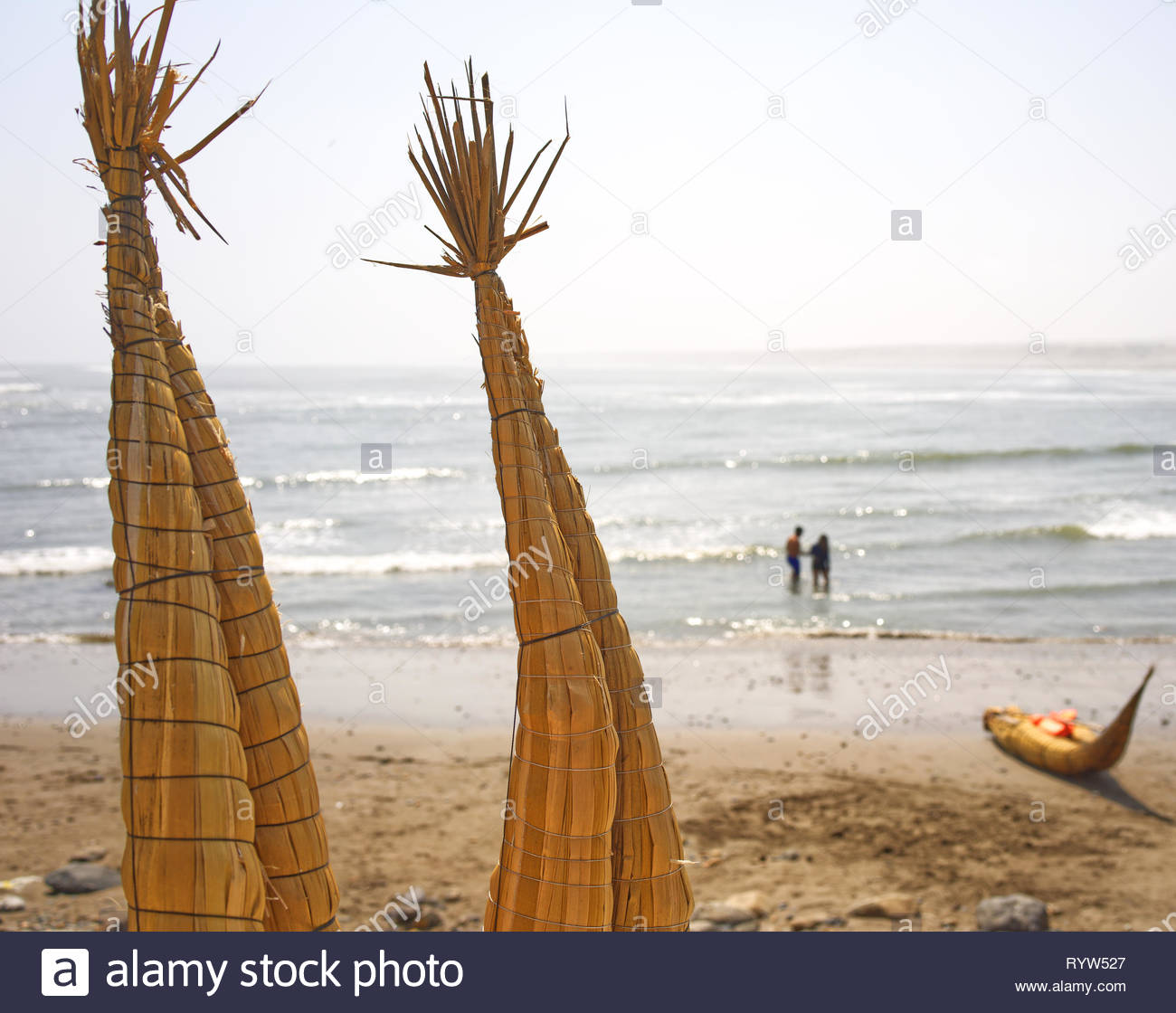 Reed boat Caballito de Totora on the beach in Huanchaco Trujillo Peru with a couple in the background. Out swimming - Stock Image