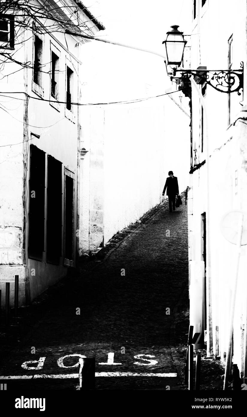 Woman in a steep alley in Lisbon, Portugal - Stock Image
