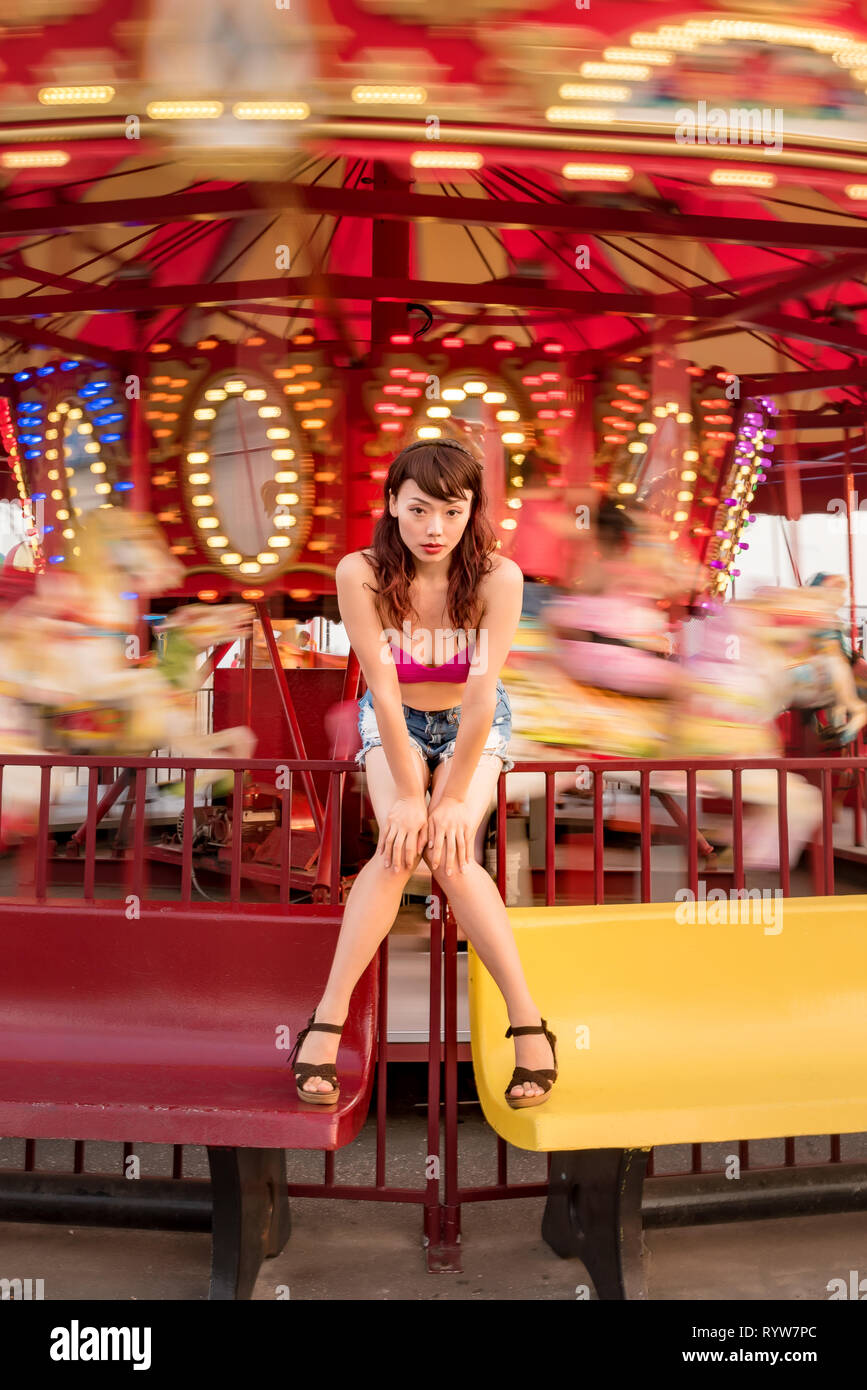 Attractive Chinese girl chilling at the carnival in Brooklyn, NY USA - Stock Image
