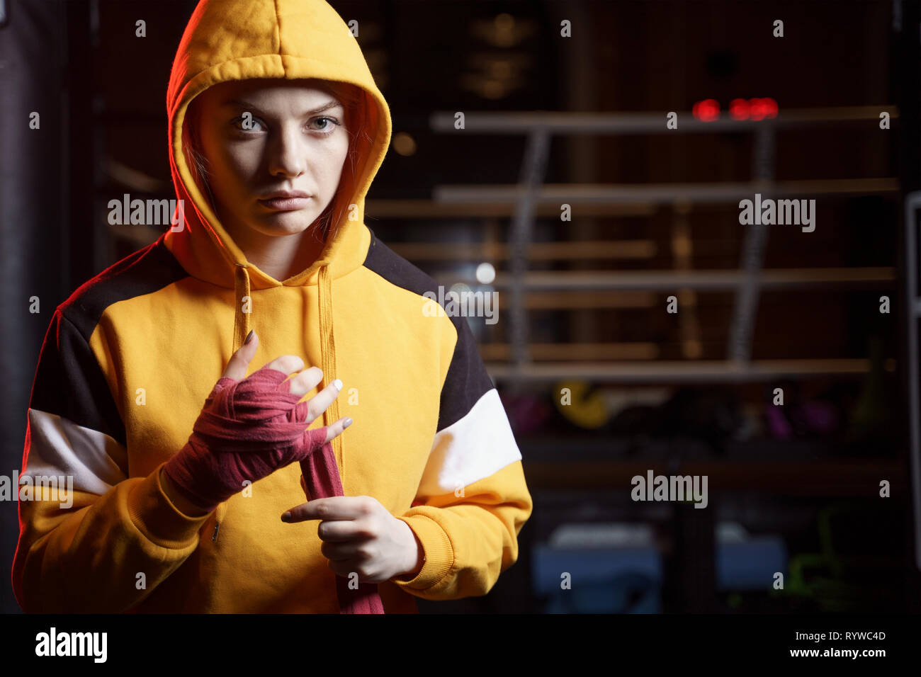 Woman boxer pulls red bandages around her hands on ring . - Stock Image