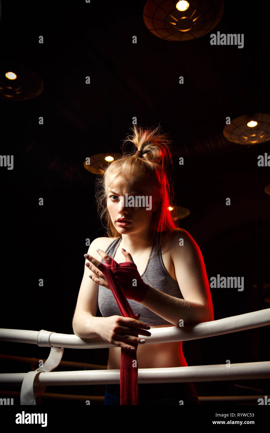 Young blonde pulls red boxing bandages around boxing ring. - Stock Image