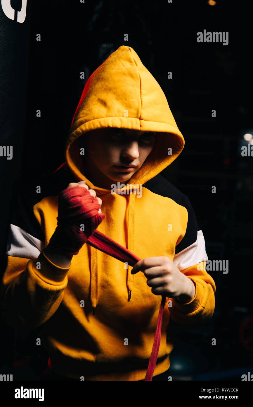 Woman boxer in yellow sweatshirt pulls red bandages on her hands. - Stock Image