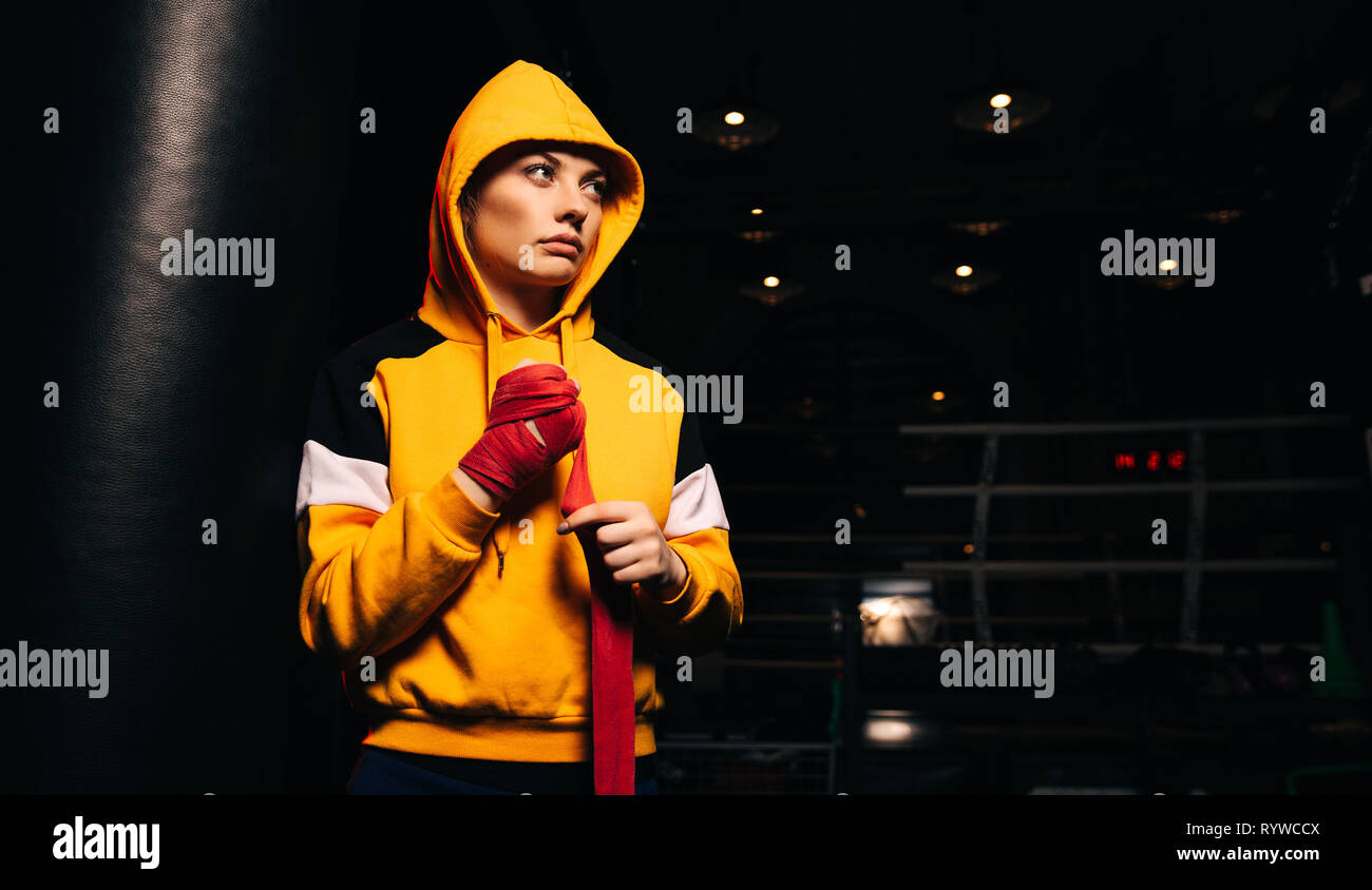 Sports girl boxer in yellow sweatshirt pulls red bandages on her hands. - Stock Image