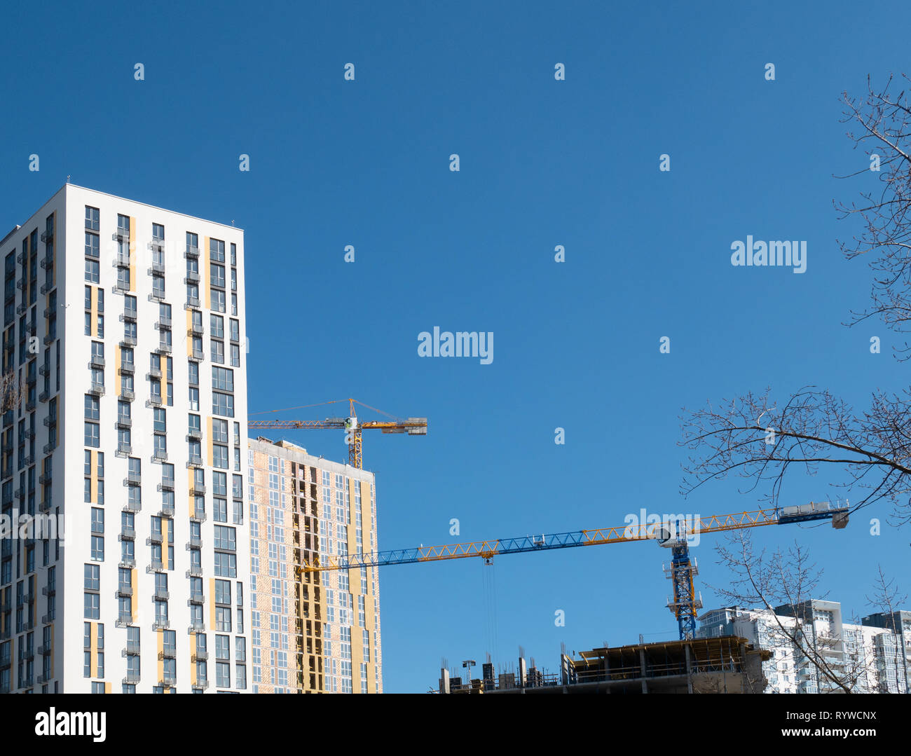 few modern freshly build residential buildings and crane at construction site. clear blue sky on background - Stock Image