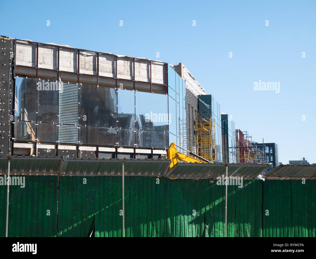 long green fence enclose construction site of small office building. outdoor image with blue clear sky on background - Stock Image