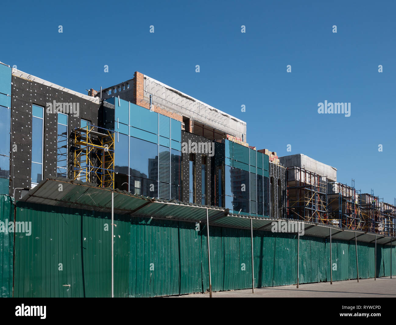 long green wooden fence at construction site. building small shopping mall store from glass, metal and concrete - Stock Image