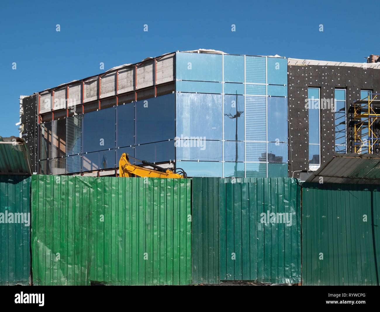 green fence in front of construction site. small office building or townhouse made from glass, metal and concrete - Stock Image