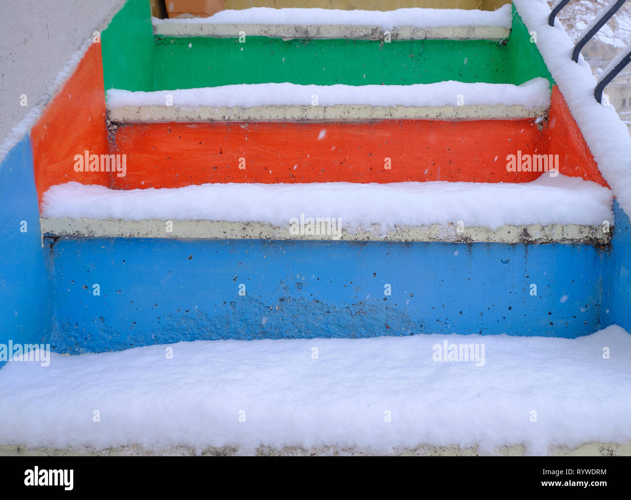 Colorful steps (blue, orange and green) covered in fresh powdery snow Stock Photo