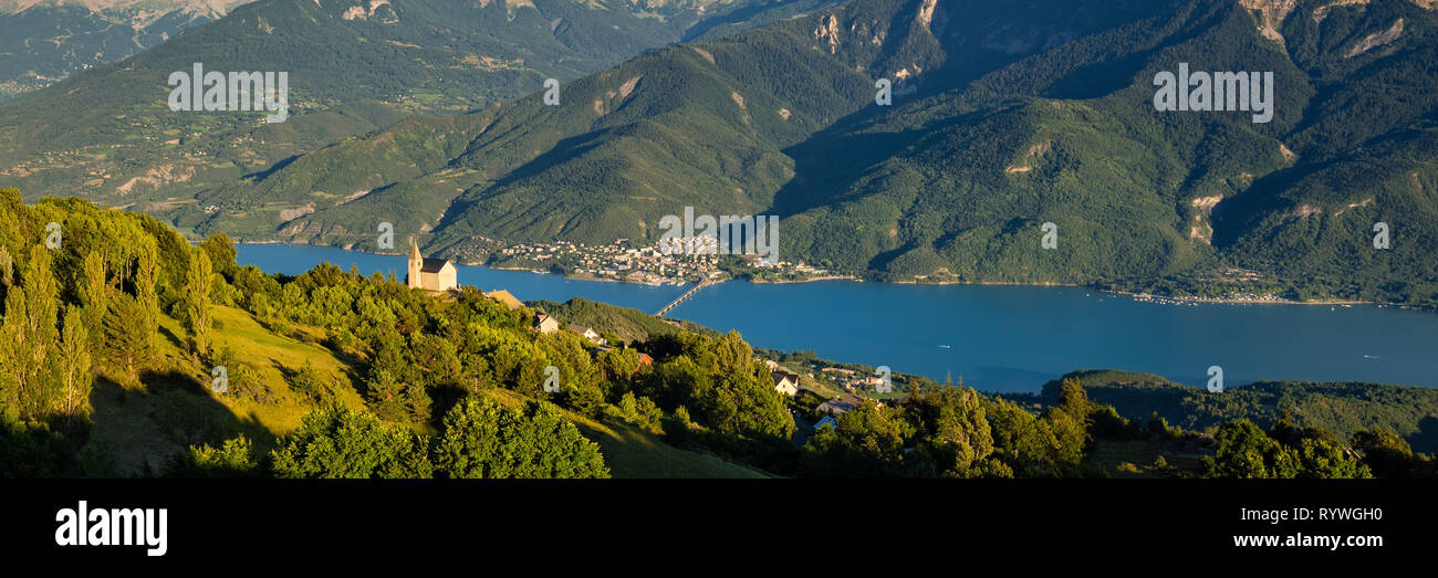 Elevated panoramic view on the Church of the village of Saint-Apollinaire and Savines-Le-Lac at sunset. Summer in the Hautes-Alpes, Alps, France - Stock Image