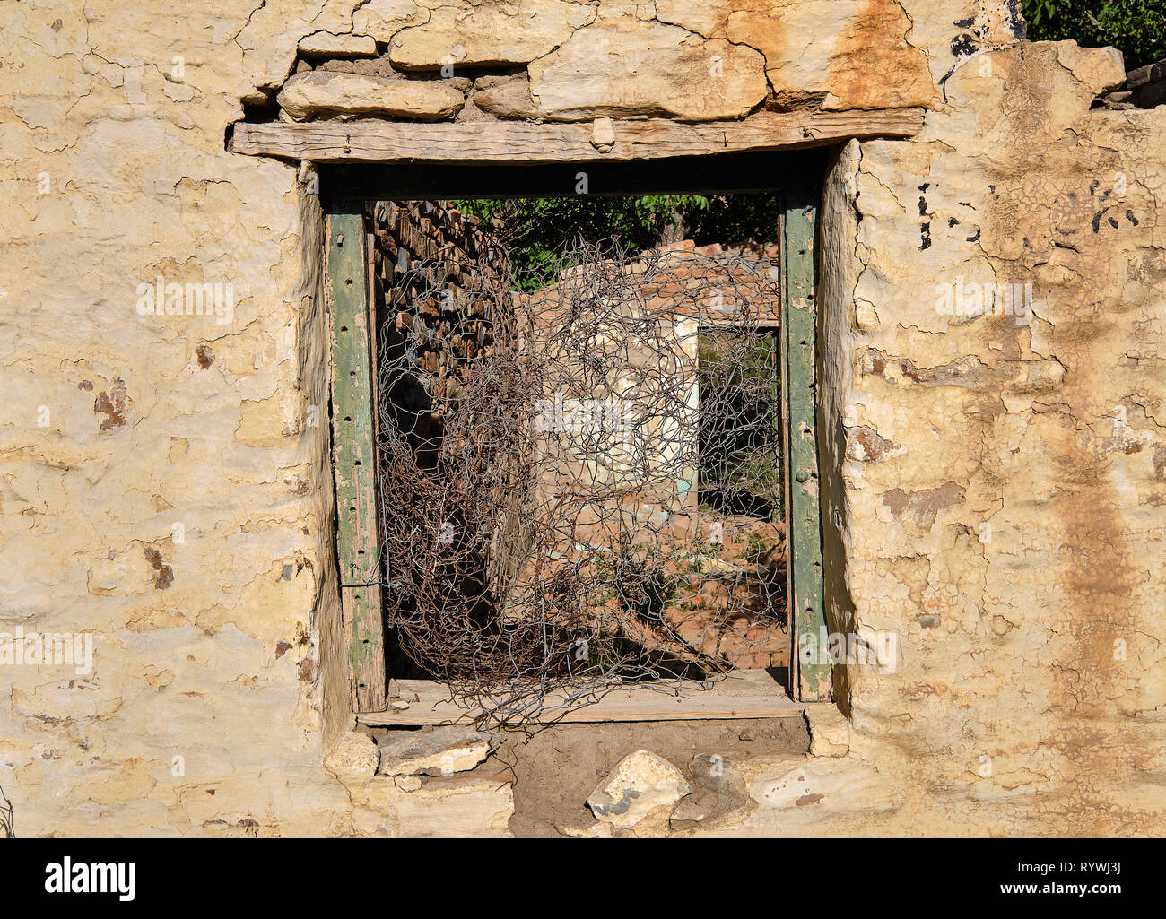 Central empty green window frame on rocky wall of abandoned house.  Through frame see barbed wires and rest of structure in ruin Stock Photo