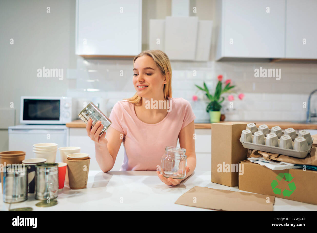 Recycling. Young smiling woman is sorting empty glass bottles and metal cans while sitting at the table with other waste at home - Stock Image
