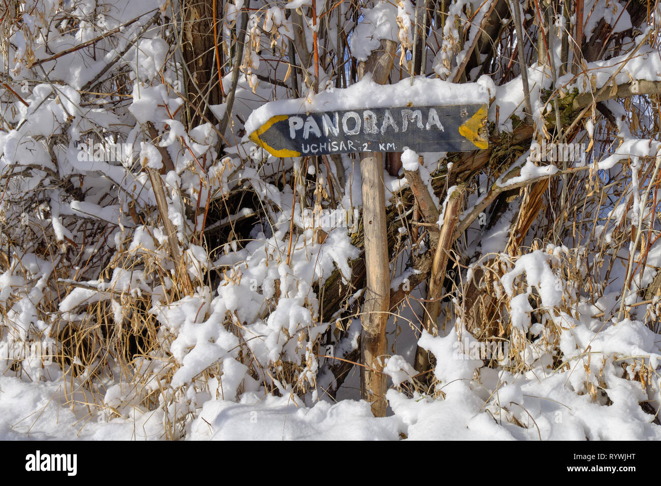 Arrow and sign pointing direction to Panoramic view of Cappadocia covered in fresh snow, surrounded by dried vegetation Stock Photo