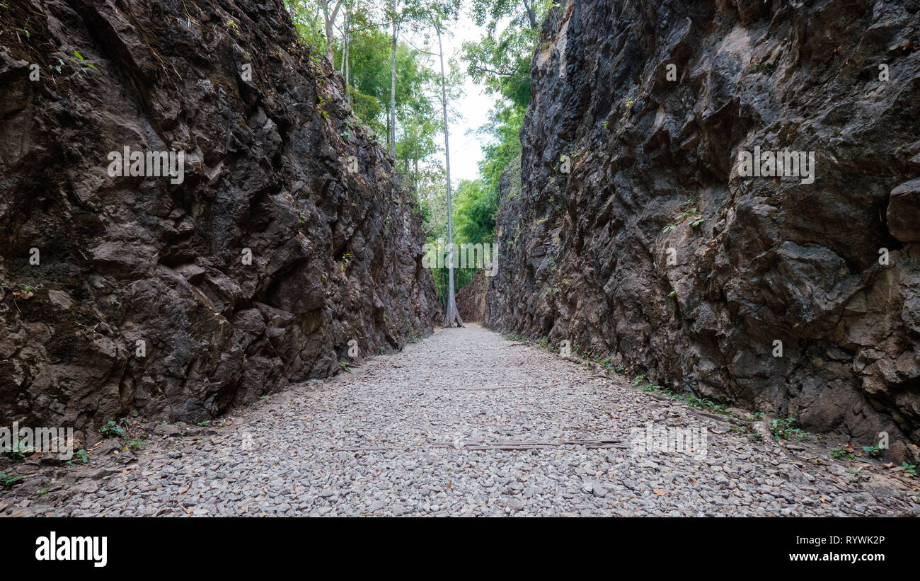 Shot of a gravel pathway that flanked by tall cliffs and rocks giving an uneasy and dangerous feeling - Stock Image