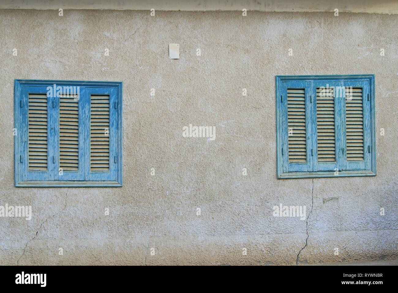 Blue shuttered windows on a house in a Nubian Village near Aswan, Upper Egypt, North Africa - Stock Image