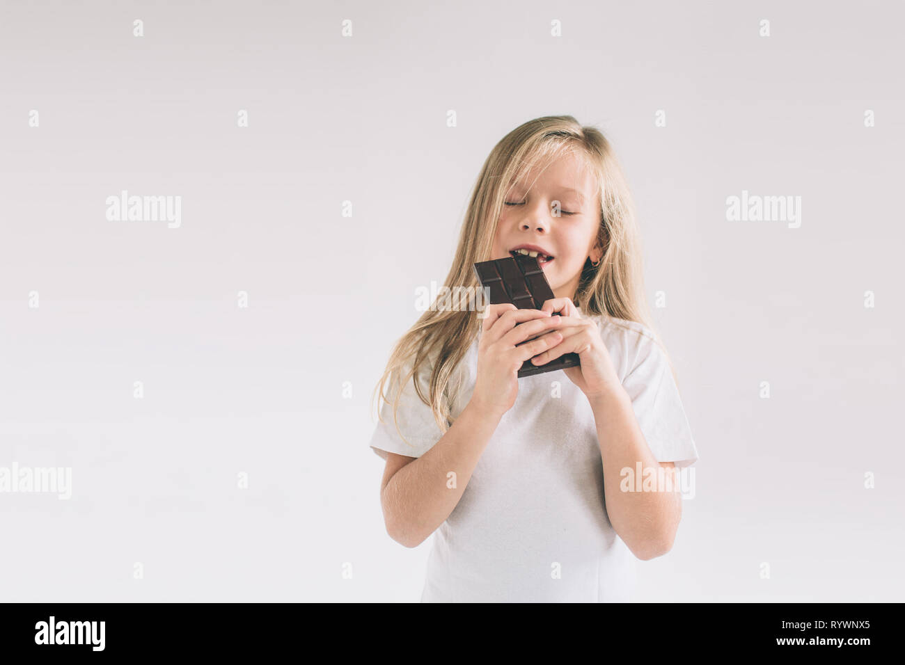 young child eating a chocolate bar. Blondy girl isolated on white background - Stock Image