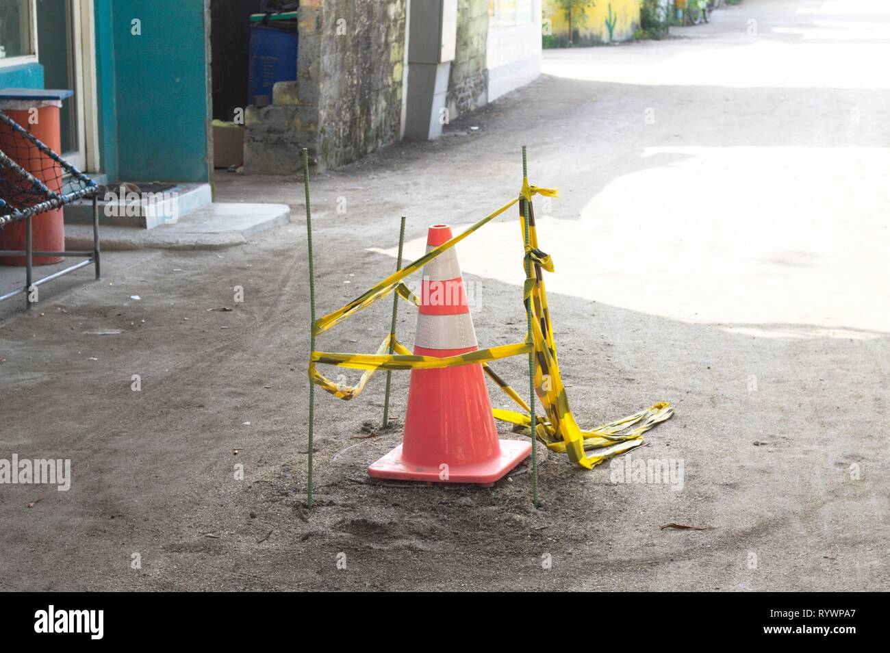 Work in progress - Isolated street cone in the street with a black and yellow net (Ari Atoll, Maldives) - Stock Image