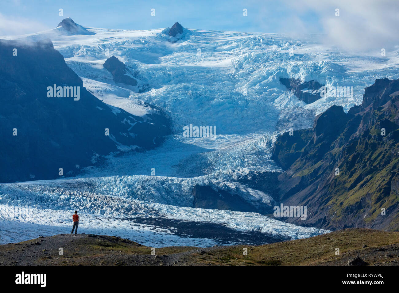 Person dwarfed by the ice fall of Kviarjokull glacier. Vatnajokull ice cap, Sudhurland, south east Iceland. - Stock Image