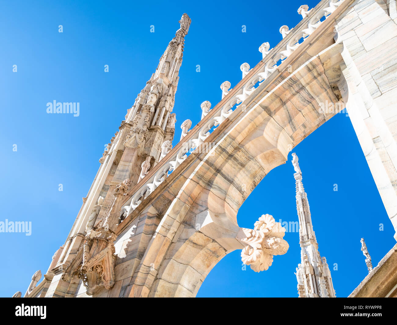 MILAN, ITALY - FEBRUARY 24, 2019: detail of decoration of Milan Cathedral (Duomo di Milano) roof in Milan in morning under blue sky. This Basilica is  - Stock Image