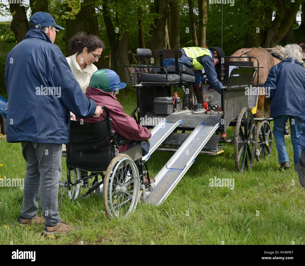 Wheelchair-bound rider being pushed up a ramp onto a carriage on a Carriage Driving day run by the Riding for the Disabled Association, Wiltshire, UK. - Stock Image