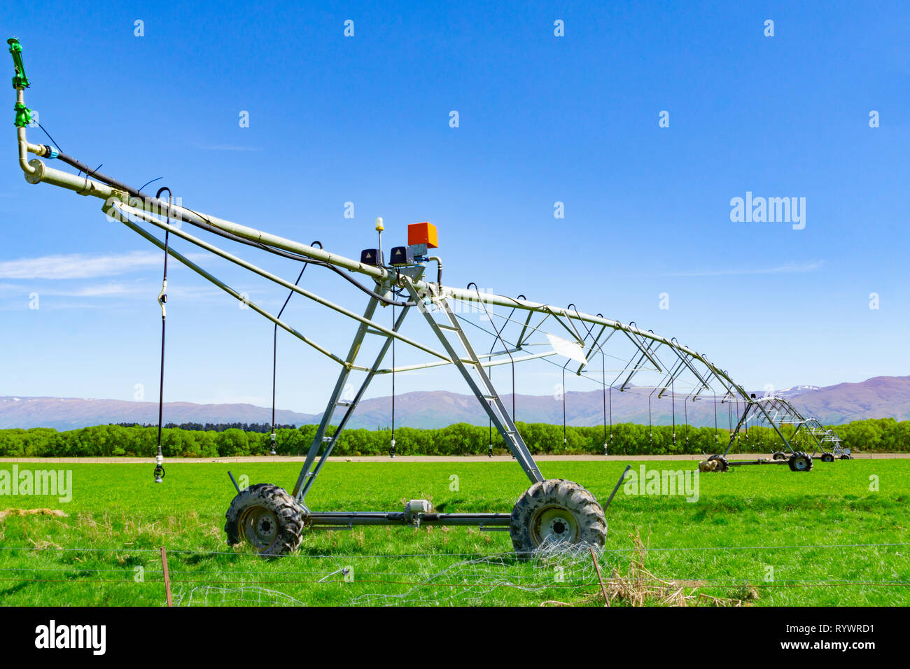 Large centre pivot irrigation system running on a farm in Canterbury, New Zealand. Long movable booms of the water distribution plant stretch across f - Stock Image