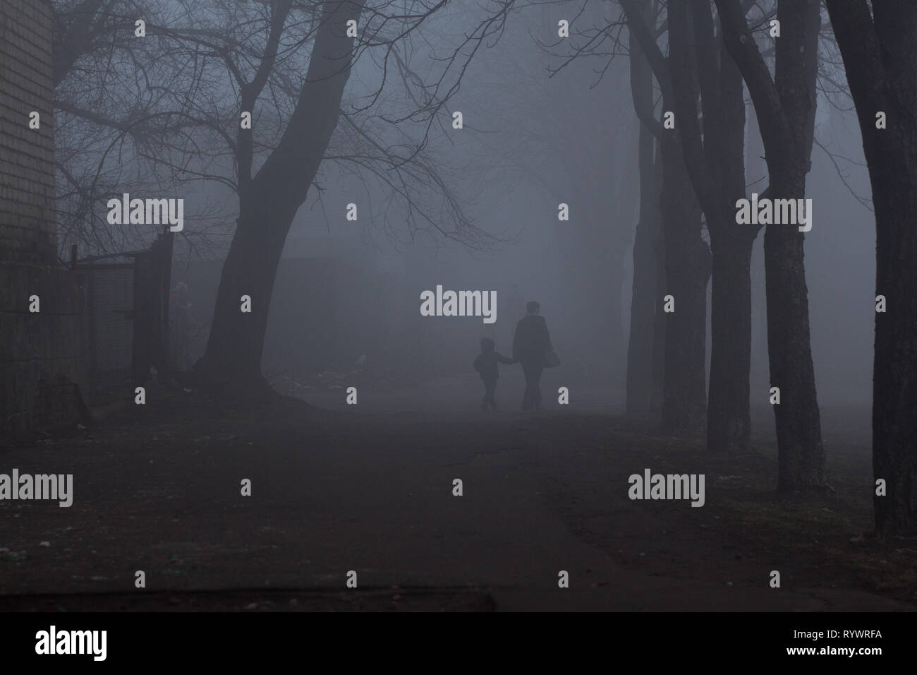 People walking on the street in the thick cryptic fog in Kriviy Rih, Dnipropetrovsk region, Ukraine - Stock Image