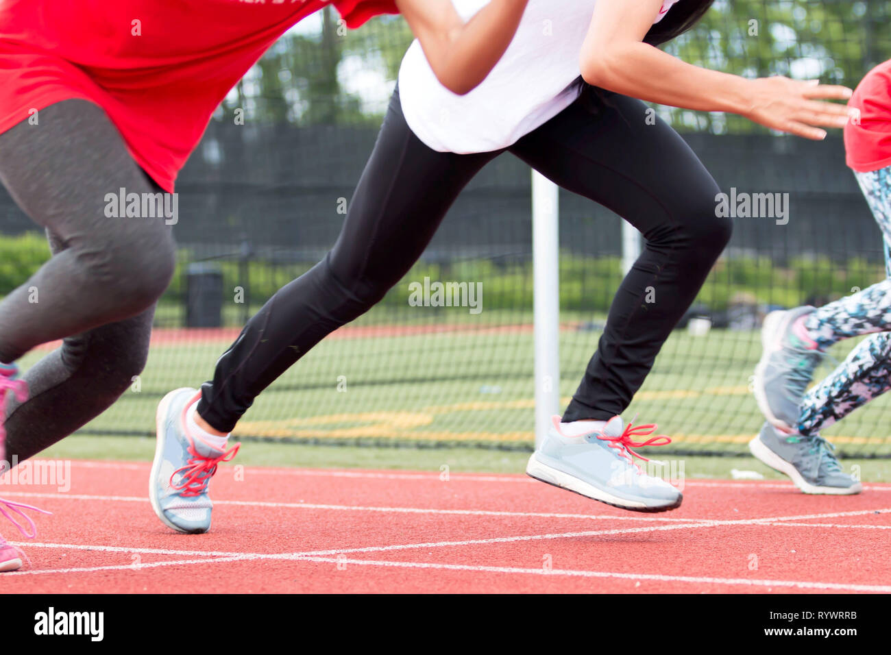Three girls race each other sprinting at high school track and field practice outside on a red track. - Stock Image