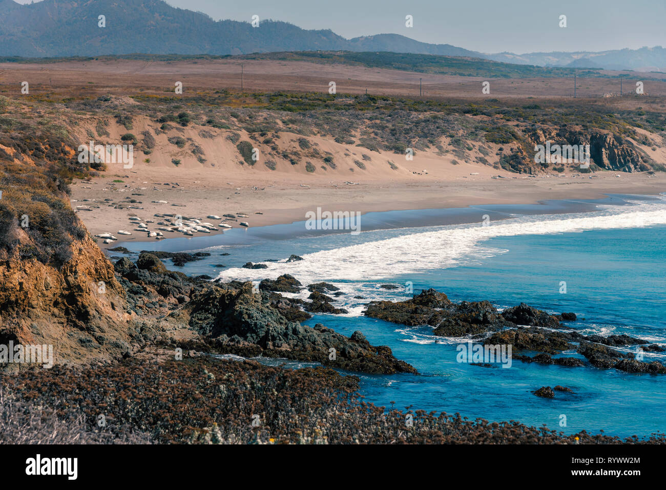 White ocean waves rolling onto sandy shoreline and beach below. Stock Photo