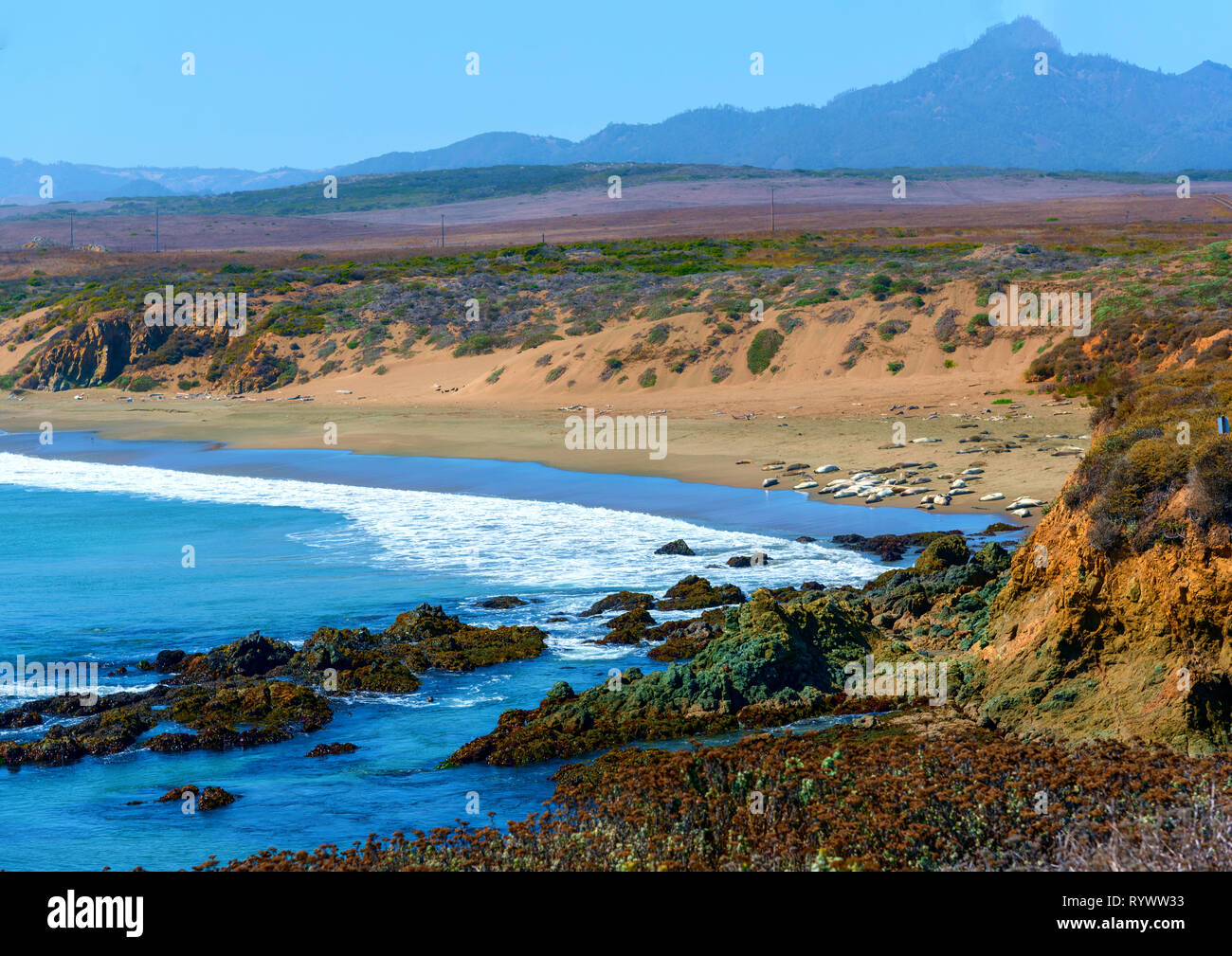 White waves rolling onto shore below, sandy beach and rocky coastline under bright blue sky. Stock Photo