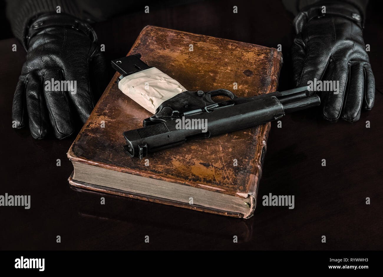 On an old book, probably a book of wisdom, a pistol whose handle is wrapped in tape. Also we see the gloved hands of someone ready to act. Stock Photo