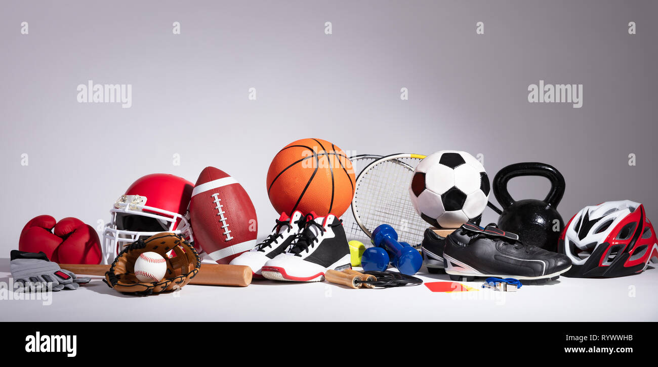 Variety Of Sport Balls And Equipment In Front Of Gray Surface - Stock Image