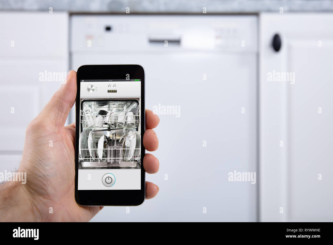 Close-up Of A Person's Hand Operating Dishwasher With Smartphone - Stock Image