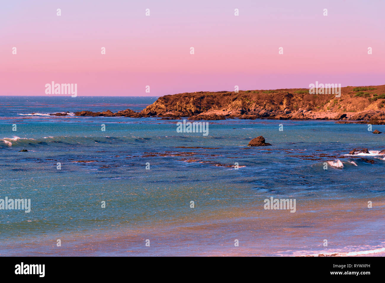 Blue Green Ocean With Small Breaking Waves Seaside Cliffs At Sunset Under Pale Orange Red Pink And Purple Sky Stock Photo Alamy