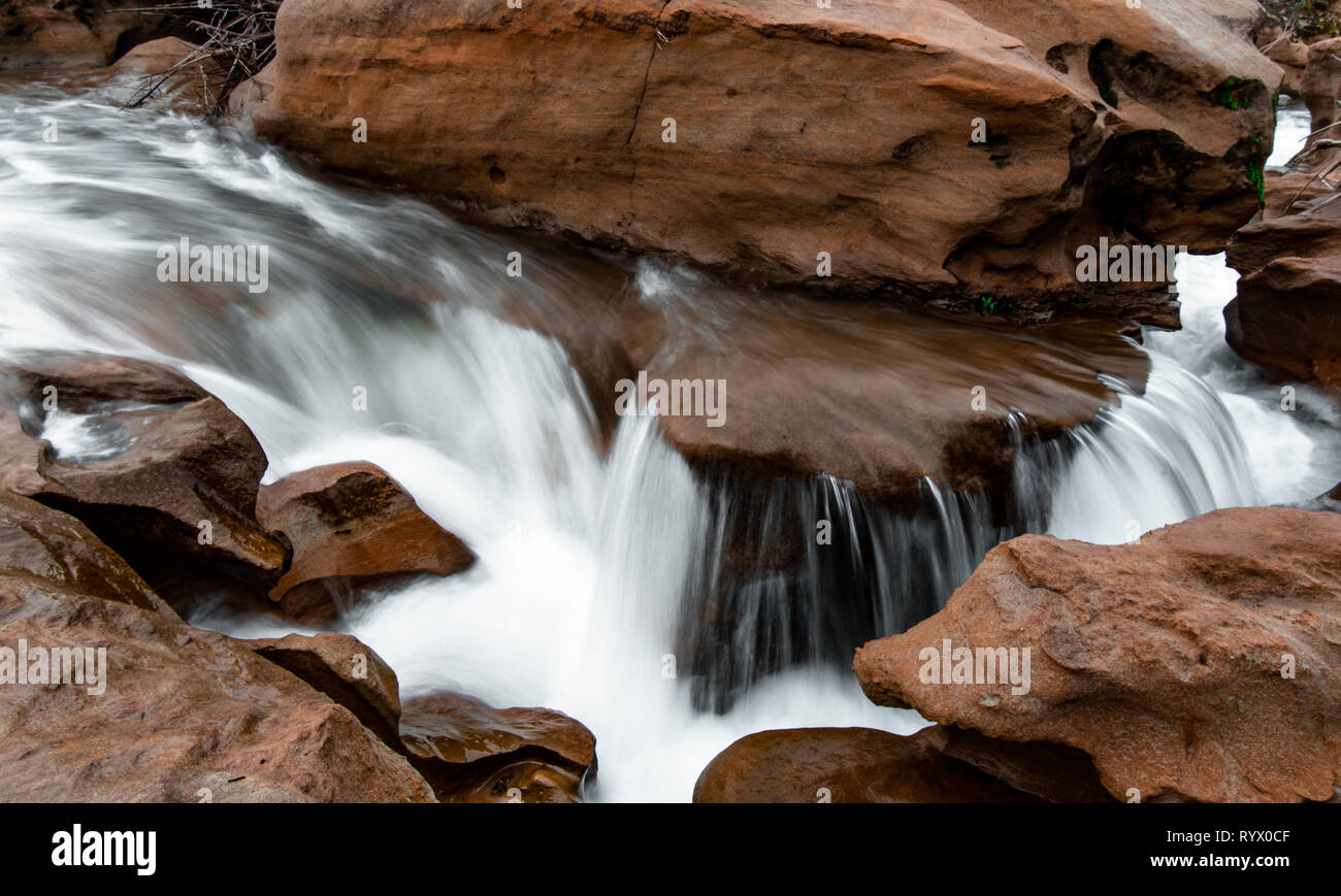 Water flowing and cascading through a sand stone slot canyon. Silky water effect with flowing blue water. Stock Photo