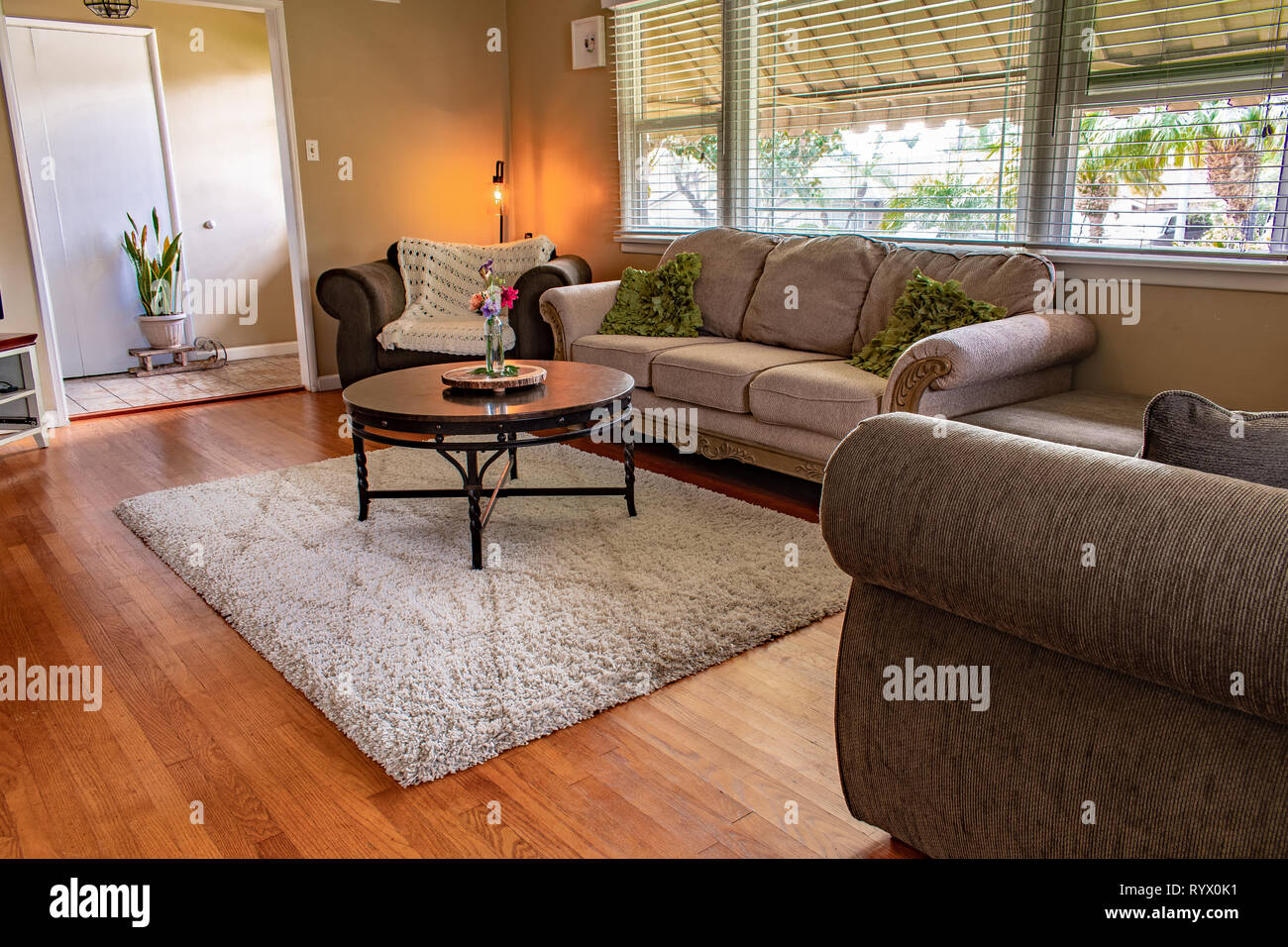 A comfortable looking family room.  Couches and rug resting on a plank hardwood floor - Stock Image