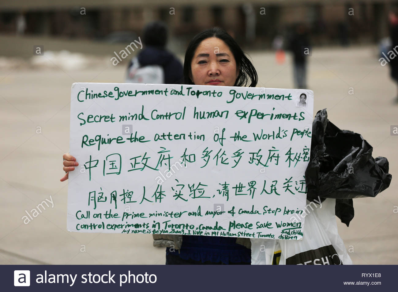Chinese woman protesting against the Chinese government and the Canadian government's alleged mind control experiments in Toronto, Ontario, Canada. - Stock Image
