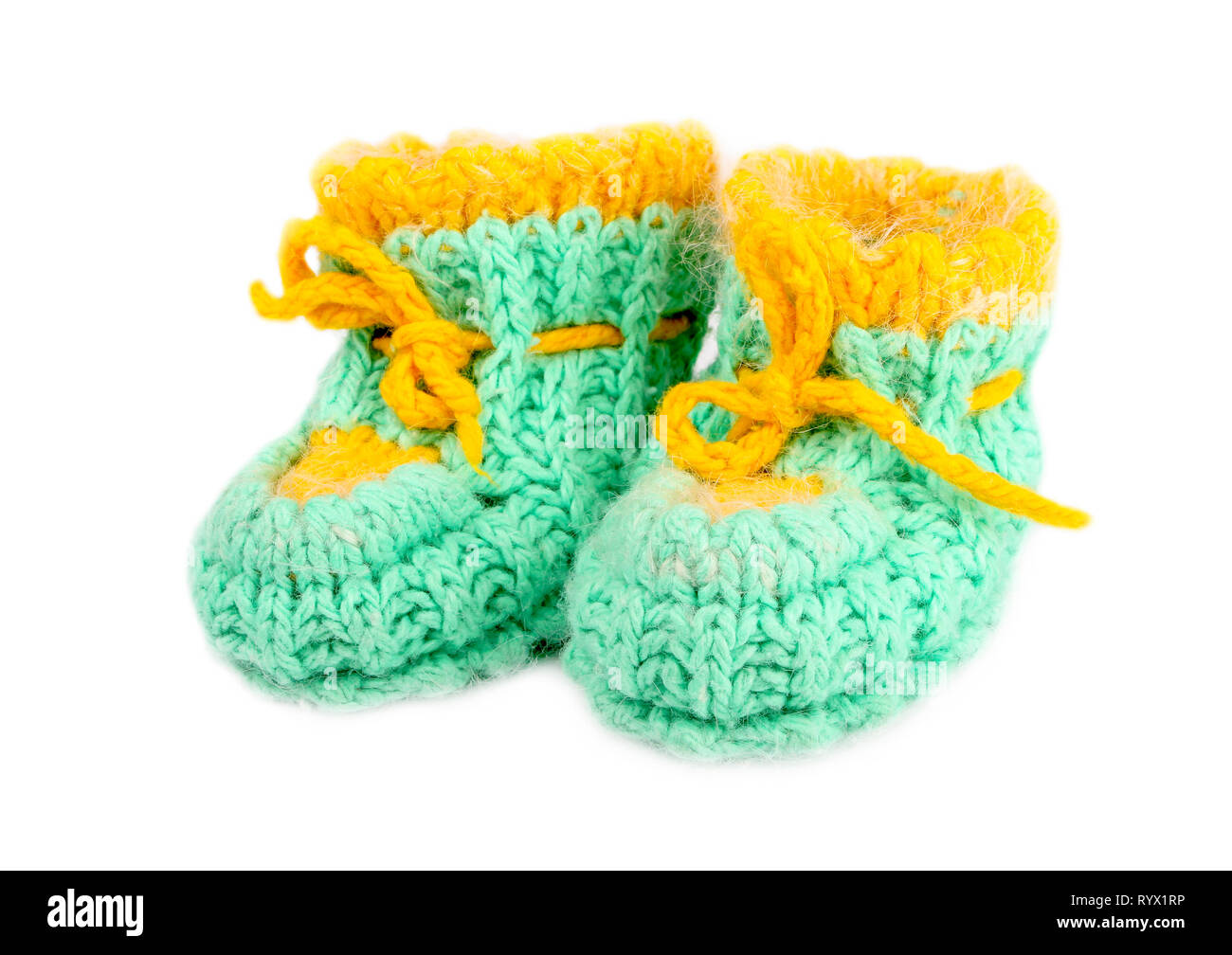 Baby woolen booties, knitted of green and yellow thread - Stock Image
