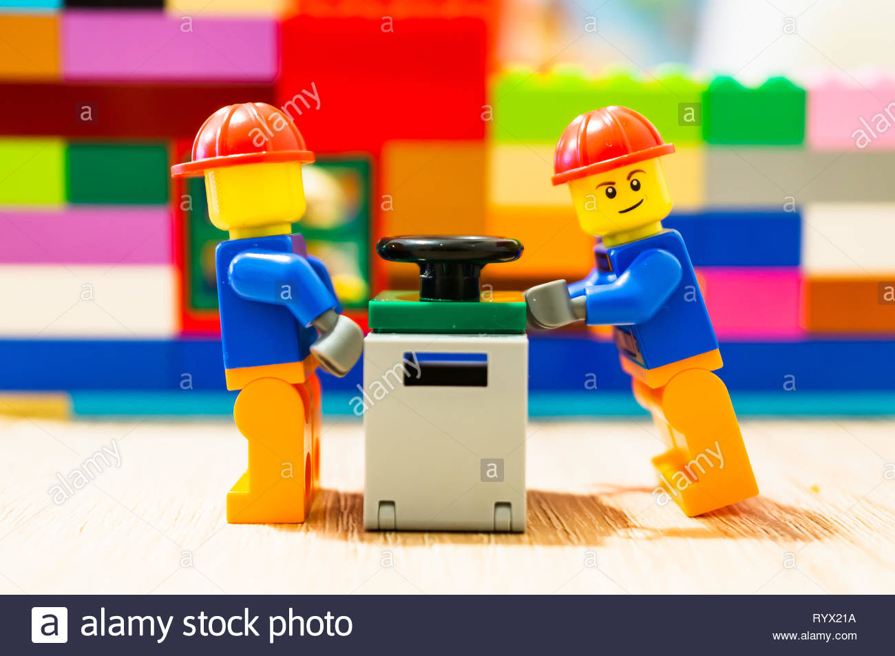 Poznan, Poland - March 14, 2019: Two Lego construction workers pushing together a safe. Stock Photo