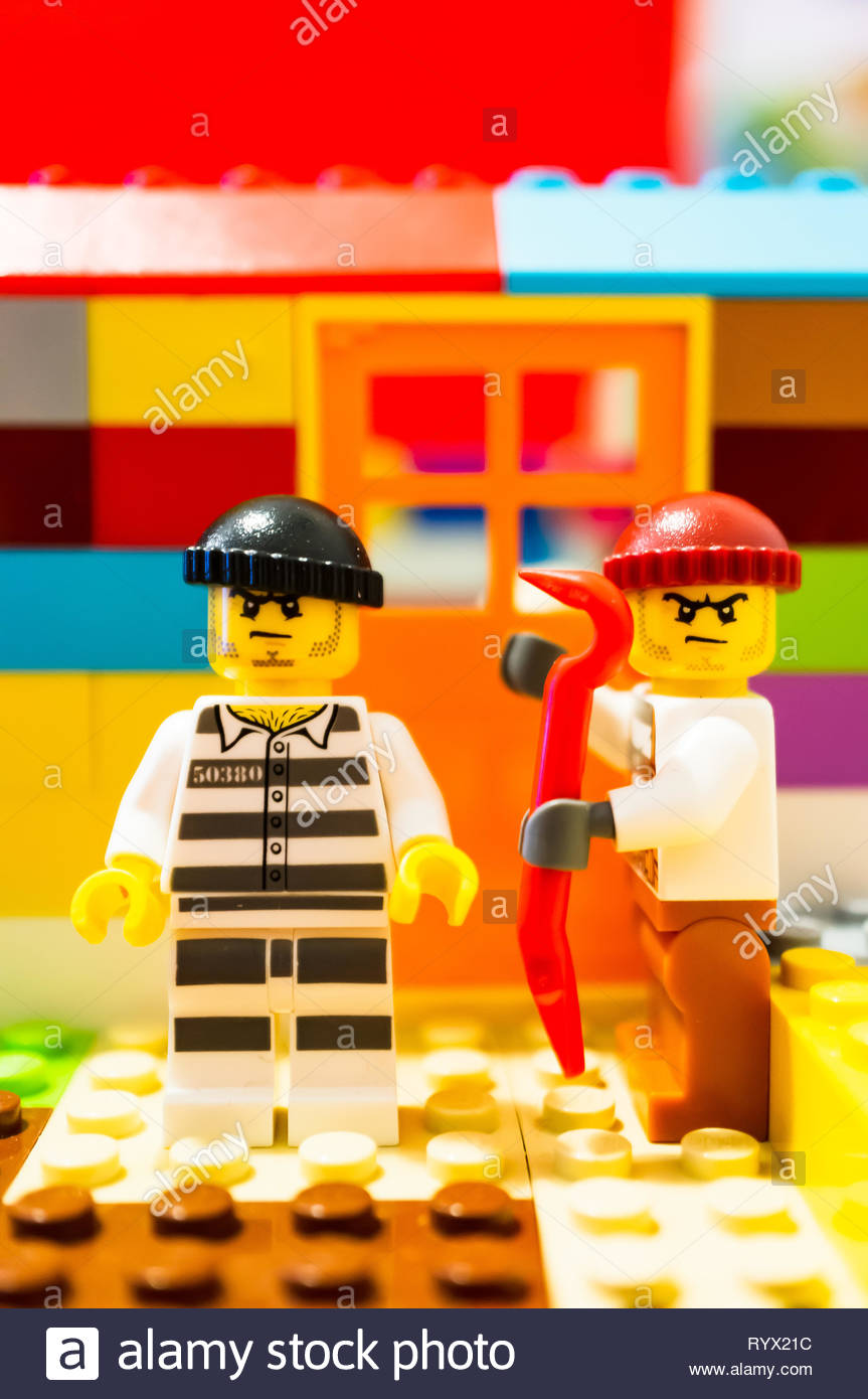 Poznan, Poland - March 14, 2019: Two Lego escaped prisoners trying to break in a house with a crowbar. Stock Photo