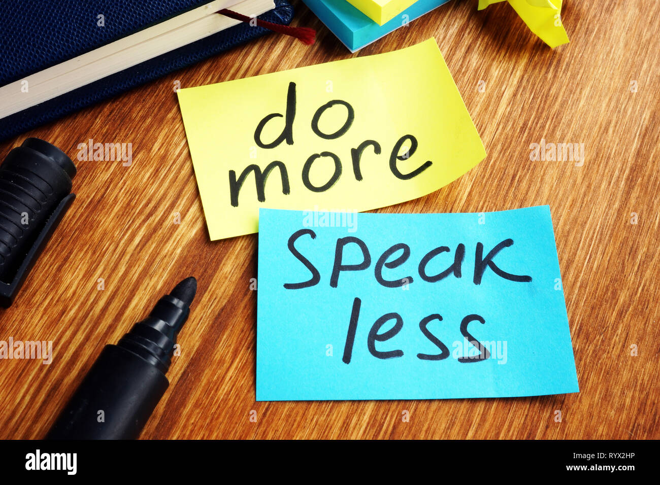 Do more speak less written on a color papers. - Stock Image