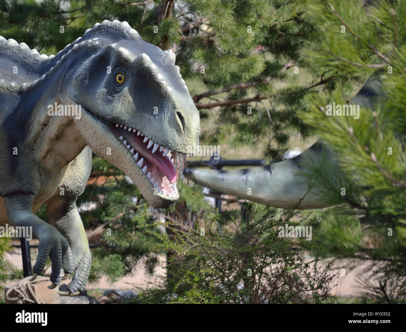 Statue, dinosaur wants to bite the tail of another dinosaur. Dino park Dinosville. Natural history center of Serbia. - Stock Image