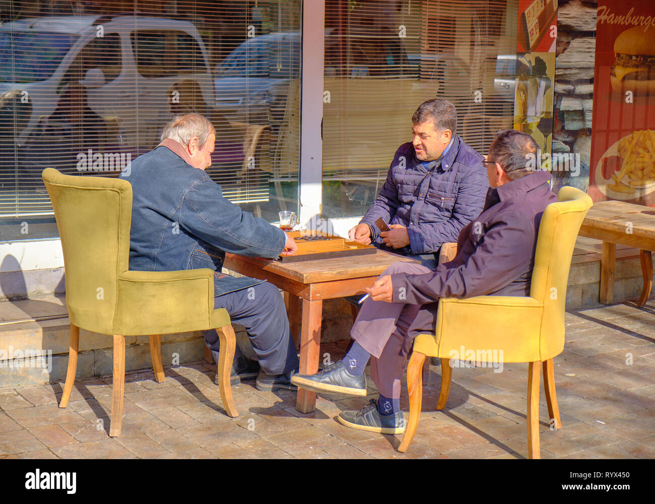 Old men playing backgammon at a cafe on old town street of Antalya, Turkey - January 3, 2019 Stock Photo