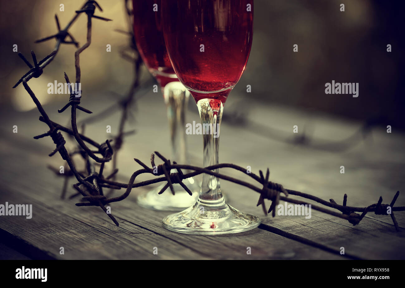Glasses with alcoholic drink and a rusty barbed wire on a wooden table. Alcoholic dependence. - Stock Image