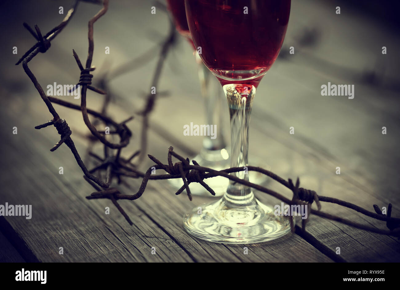 Rusty barbed wire and glasses with red wine on a table.  Alcoholic dependence. - Stock Image