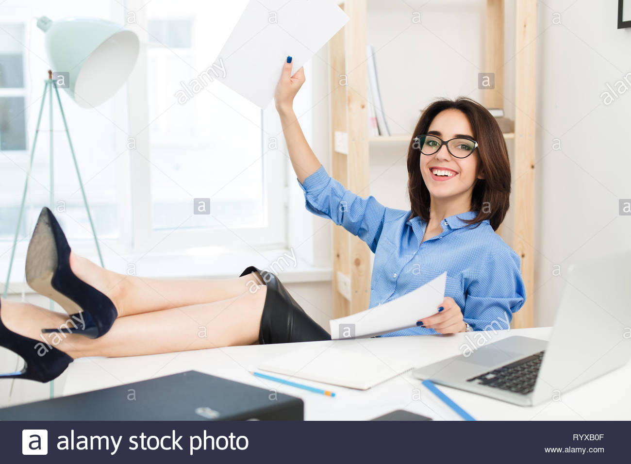 A pretty brunette girl in blue shirt is sitting at the table in office. She crossed her legs on the table. She looks very happy with papers in hands. - Stock Image