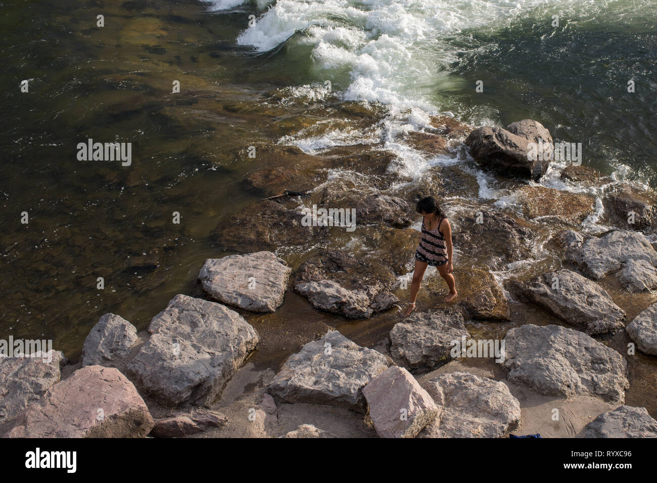 A woman enjoys skipping rocks and observing the kayakers at Brennan's Wave in Missoula, Montana - Stock Image