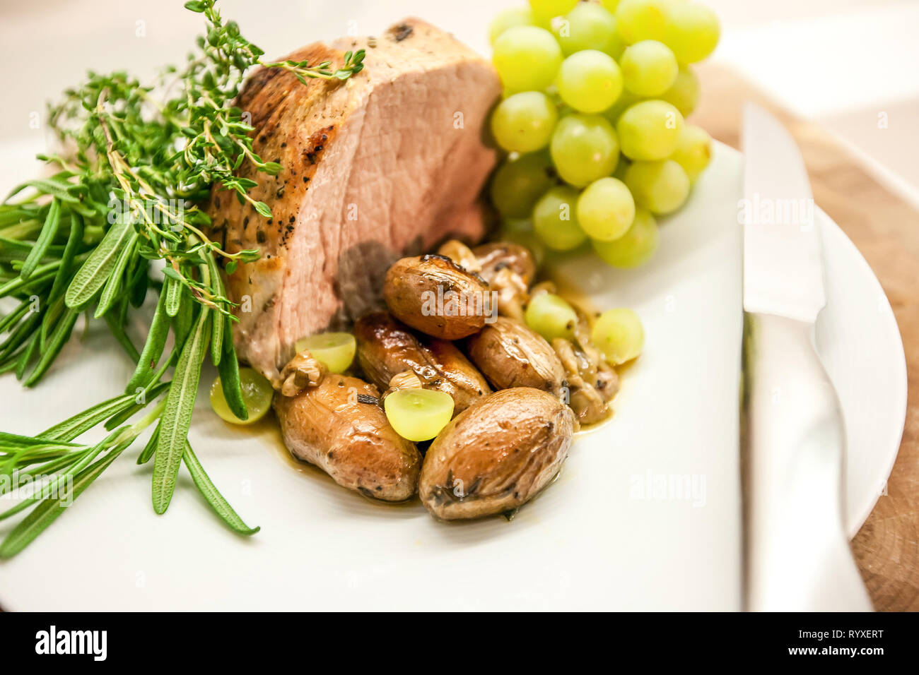 One piece roasted bacon with roasted garlic, grapes, figs, and fresh rosemary. Stock Photo